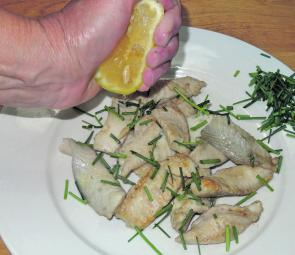 To serve, place the mackerel fillets on a plate and spoon the herb butter sauce over the fillets. A squeeze of lemon lifts the tastes in the dish.