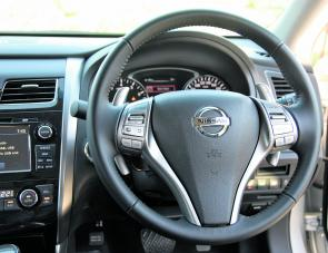 Many of the Altima's steering wheel controls are visible in this image including the shifter paddles.