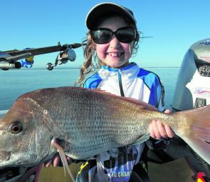 Asher Blake displays the nice snapper she caught while fishing with here dad.